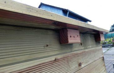 Damit diese Umrandung stabil ist: Holzreste, etwa im Abstand von einem Meter bündig mit dem obersten Brett anschrauben, Bretter anpassen und auflegen und von oben mit Schrauben fixieren.
