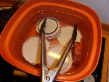 Auch die Deckel benötigen ein heißes Wasserbad. Mit einer Grillzange kann man sie ideal aus dem heißen Wasser rausnehmen. Tipp: Vom Deckel gut das Wasser abschütteln.