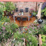 Garten neu anlegen: Kleiner Garten mit vielen Blühpflanzen und Hochbeeten