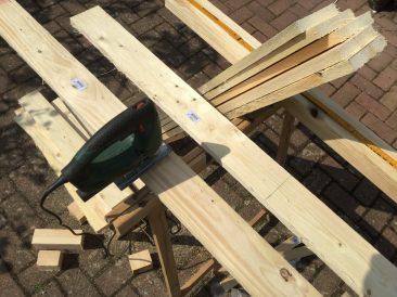 """Erstmal Holz besorgen und sägen. Hier ist es, wie im Text beschrieben, hilfreich: Eine Latte oder ein Brett exakt ausmessen und dieses als Vorlage auf die folgenden Bretter legen und das Maß anzeichnen. Aus den """"Abfallbrettern kann man später etwas anderes bauen."""