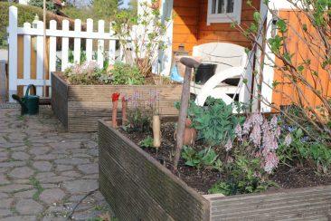 2 Recycling-Hochbeete. Aus dem alten, noch intakten Holz der abgerissenen Terrasse wurden 2 Hochbeete für Blühpflanzen, die auf dem Pflaster vor dem Gartenhaus stehen.